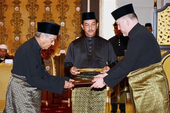 Dr Mahathir Mohamad receives the instrument of appointment from the Yang di-Pertuan Agong, Sultan Muhammad V